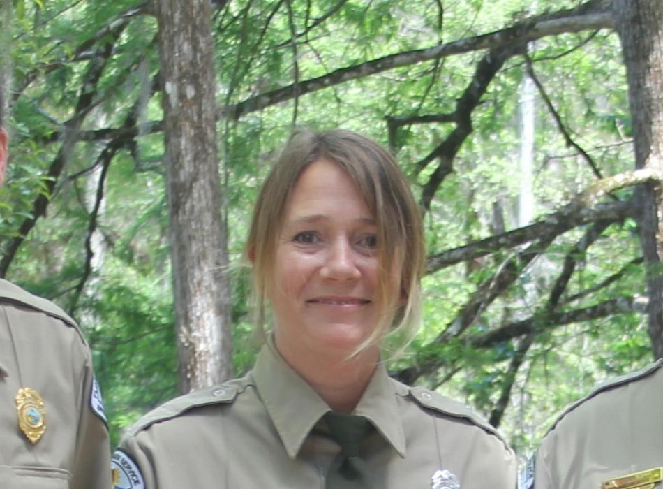 a blonde woman stands in front of trees in a park service uniform
